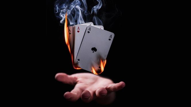 A hand holding levitating, burning playing cards