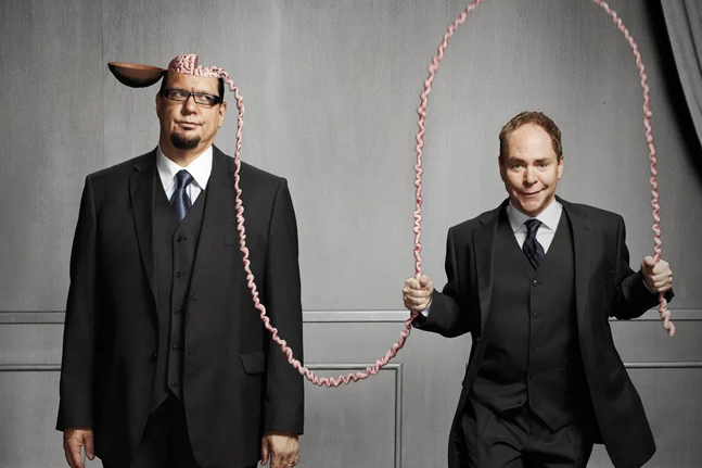 Teller jumping rope with a pink cord coming from Penn's head