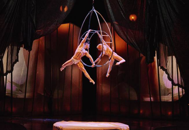 Two Zumanity performers dangling from a ring above the stage