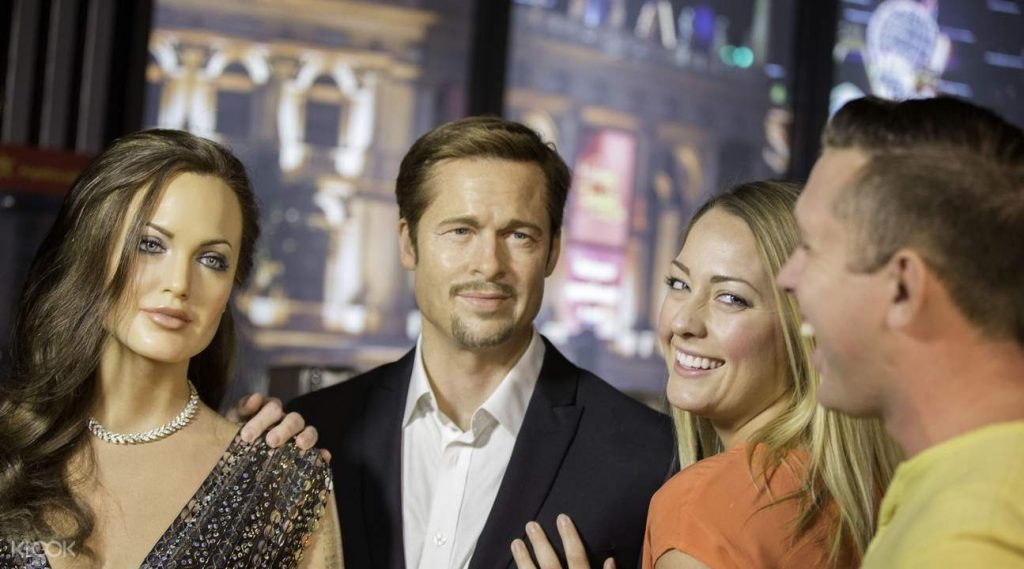 Tourists posing for a photo with wax figures of Angelina Jolie and Brad Pitt