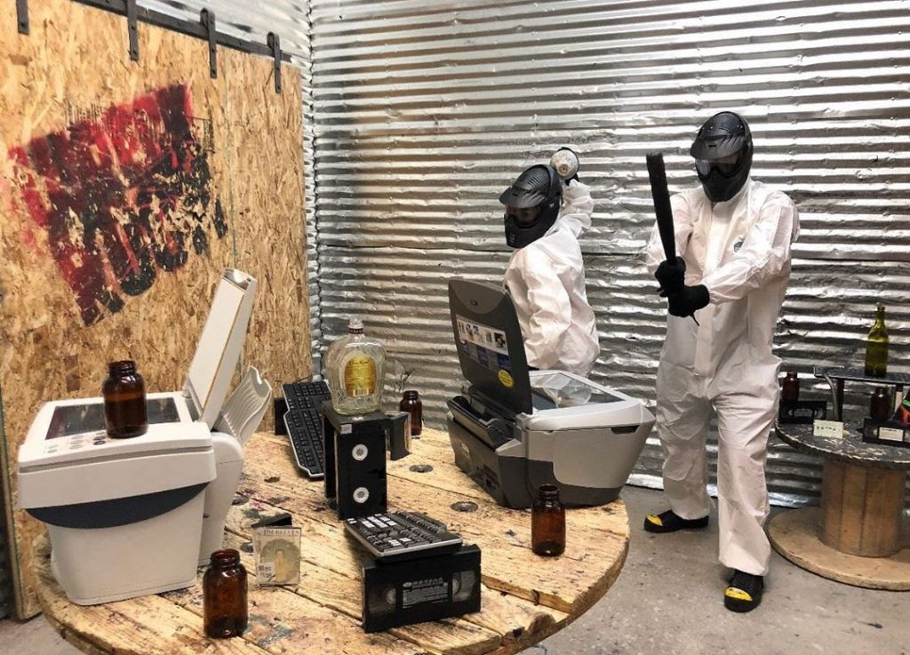 Two people breaking appliances in a rage room