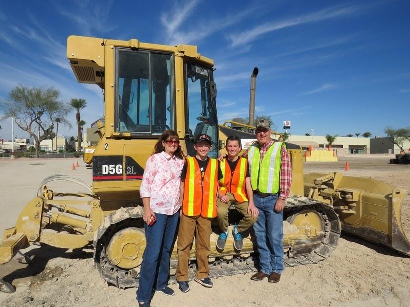 Close up of a family posing next to a bulldozer