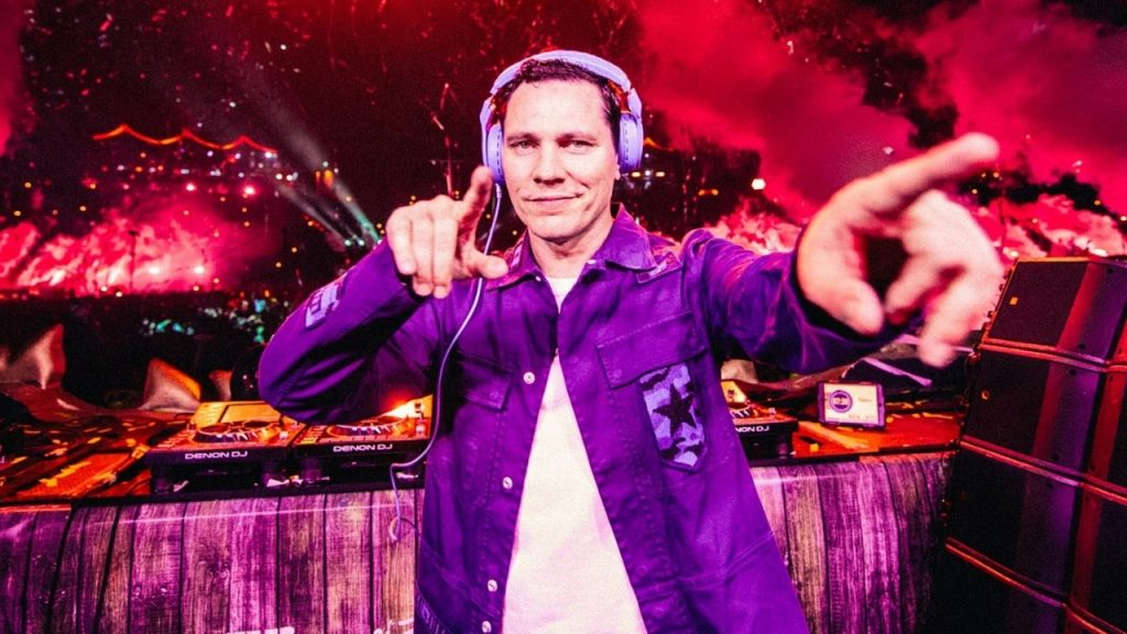 Tiësto performing and pointing to a camera at a concert