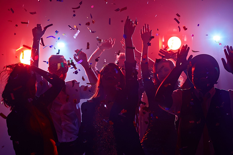 People dancing at a club while confetti flutters around