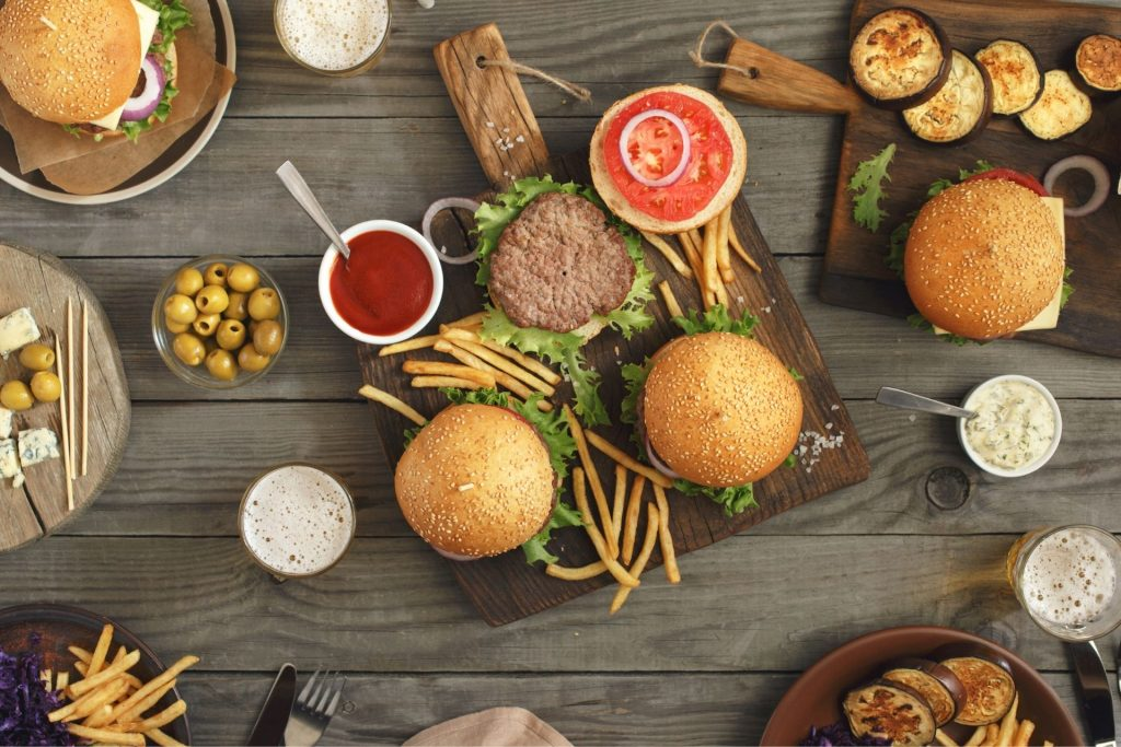 A flat lay photo of some of the best burgers in Las Vegas and other fast food on a table.